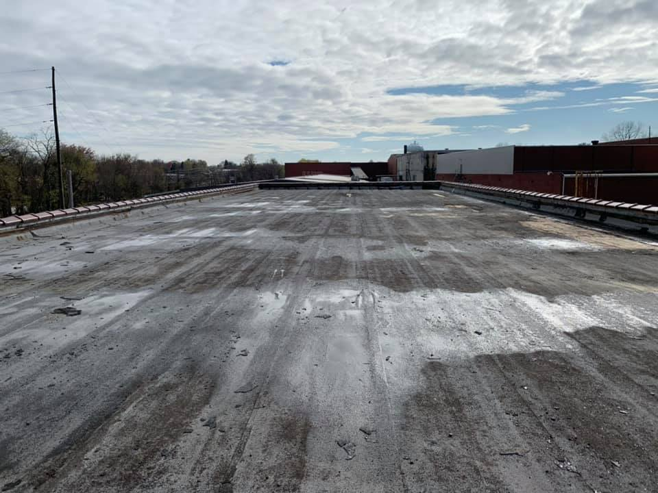 a black roof in need of commercial roofing in Raleigh, NC