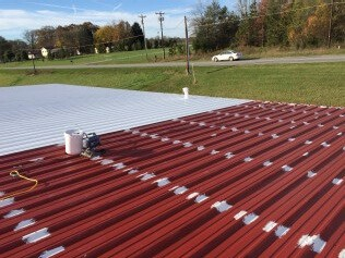 Roof restoration in progress, turning a red roof to energy efficient white